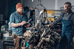 2 люд ремонтируя автомобиль в гараже Стоковые Фотографии RF