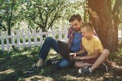 2 люд сидят совместно под деревом и смотрят экран ` s компьтер-книжки Мальчик держит компьтер-книжку на его коленях лучей стоковые изображения
