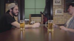 2 люд сидя на таблице в баре, приниманнсяом за армрестлинге Один парень выигрывает, другое теряет, и оба выпивают пиво Парни акции видеоматериалы