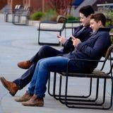 2 люд смотря их телефон черней стоковые изображения