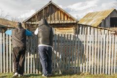 2 люд стоят около деревянной загородки и старых деревянных зданий Сельский образ жизни Стоковая Фотография