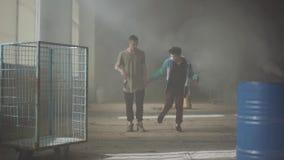 2 люд танцуя в темной и пылевоздушной комнате получившегося отказ здания Подростки делая движение танца одновременно, держащ видеоматериал