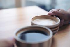 2 люд clink кофейные чашки на деревянном столе в кафе стоковое фото rf