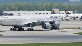 Люфтганза строгает делающ такси на взлётно-посадочная дорожка в авиапорте Мюнхена, MUC сток-видео