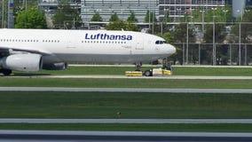 Люфтганза строгает делающ такси на взлётно-посадочная дорожка в авиапорте Мюнхена, MUC
