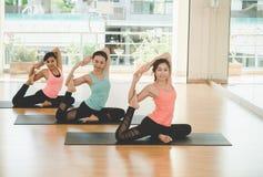Люди Азии практикуя и работая жизненно важные размышляют йога в классе Стоковая Фотография RF