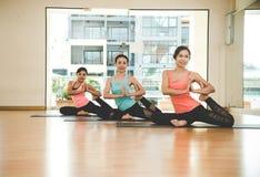 Люди Азии практикуя и работая жизненно важные размышляют йога в классе Стоковое фото RF