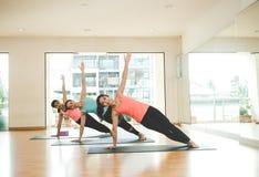 Люди Азии практикуя и работая жизненно важные размышляют йога в классе Стоковые Фото