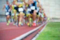 Люди атлетики бежать на поле следа стоковое фото rf