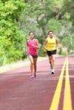 Люди бежать на дороге - бегуны спорта и фитнеса стоковое изображение
