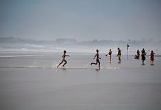 Люди бежать на песке Стоковые Изображения