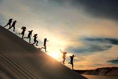 Люди бежать от горы на заходе солнца Стоковые Изображения