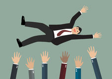 Люди бросают бизнесмена в воздухе Стоковые Фотографии RF