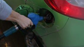Люди вручают используя бензонасос к автомобилю зеленого цвета заполнения с топливом, концом вверх акции видеоматериалы