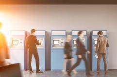 Люди в зале банка около машины ATM Стоковое Изображение