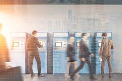 Люди в зале банка около ATM подвергают механической обработке, тонизированный Стоковое Изображение RF