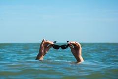 Люди в море держа стекла воды стоковое фото rf