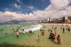 Люди в пляже наслаждаясь волнами Стоковая Фотография