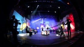 Люди в студии ТВ павильона Снимать телепередачу Силуэты работников и машинного оборудования телевидения редакционо акции видеоматериалы