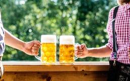 Люди в традиционных баварских одеждах держа кружки пива Стоковое Фото