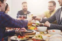 Люди говорят стекла clink приветственных восклицаний на праздничном официальныйе обед таблицы стоковое изображение