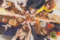 Люди говорят стекла clink приветственных восклицаний на праздничном официальныйе обед таблицы стоковое фото