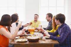 Люди говорят стекла clink приветственных восклицаний на праздничном официальныйе обед таблицы стоковые изображения