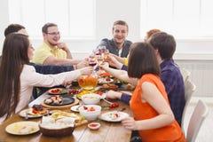 Люди говорят стекла clink приветственных восклицаний на праздничном официальныйе обед таблицы стоковая фотография