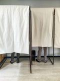 Люди голосуя в кабинах для голосования на избирательном участке Стоковое Фото