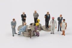 Люди группы миниатюрные на монетках стоковые фото