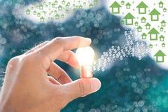 Люди держат электрические лампочки с солнцем в дневном времени, с фонами и домом bokeh в облаке используя обои или предпосылкой д Стоковое Изображение RF