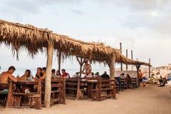 Люди есть на пляжном ресторане стоковое изображение