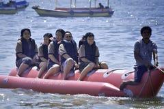 Люди ехать на шлюпке банана в Бали приставают к берегу Стоковое Изображение RF