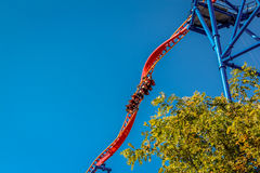Люди ехать страшная переплетая стальная американская горка на парке атракционов Стоковые Фотографии RF