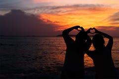 Люди делают символ сердца с рукой на сумраке Стоковые Фотографии RF