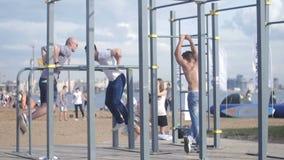 Люди делая прочность работают на спортзале тяги-вверх на акции видеоматериалы