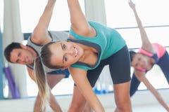 Люди делая тренировку фитнеса силы на занятиях йогой Стоковые Изображения