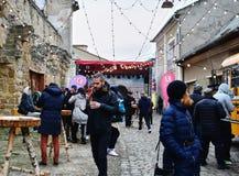 Люди едят еду улицы и имеют горячее питье на варианте зимы фестиваля еды улицы Стоковые Фото