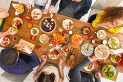 Люди едят здоровые еды на, который служат официальныйе обед таблицы Стоковые Изображения RF