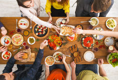 Люди едят здоровые еды на, который служат официальныйе обед таблицы Стоковые Фотографии RF