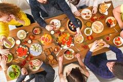 Люди едят здоровые еды на, который служат официальныйе обед таблицы Стоковые Изображения