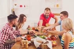 Люди едят пиццу на праздничном официальныйе обед таблицы Стоковое Изображение RF