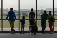 Люди ждать их полет на авиапорте Стоковые Изображения