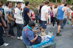 Люди играя музыку для призрения денег на улице воскресенья идя Стоковая Фотография
