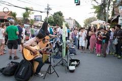 Люди играя музыку для призрения денег на улице воскресенья идя Стоковые Изображения