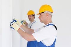 Люди измеряя стену с лентой Стоковое Изображение RF