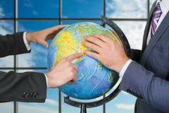 Люди изучая глобус около окна Стоковое фото RF