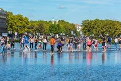 Люди имея потеху в фонтане зеркала в Бордо, Франции Стоковая Фотография RF