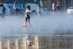 Люди имея потеху в фонтане зеркала в Бордо, Франции Стоковое Изображение RF