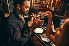 Люди имея потеху с пить на ночном клубе Стоковые Изображения